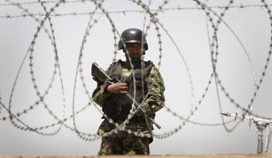 An Afghan soldier, seen through barbed wire, stands guard on the roof of one of the gates to Kabul International Airport following a shooting incident on Wednesday, April 27, 2011, in Kabul, Afghanistan, in which nine Americans were killed by an Afghan army officer. (AP Photo/Musadeq Sadeq)