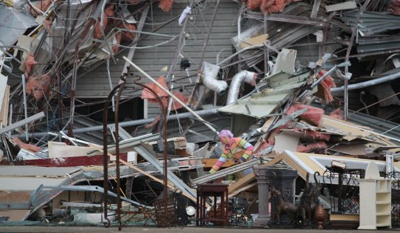 A woman sifts through the destruction of a former T Mobile office after a tornado struck, Wednesday, April 27, 2011, in Tuscaloosa, Ala. The wave of severe storms laced with tornadoes strafed the South on Wednesday, killing at least 16 people around the region and splintering buildings across swaths of an Alabama university town. (AP Photo/Caroline Summers)