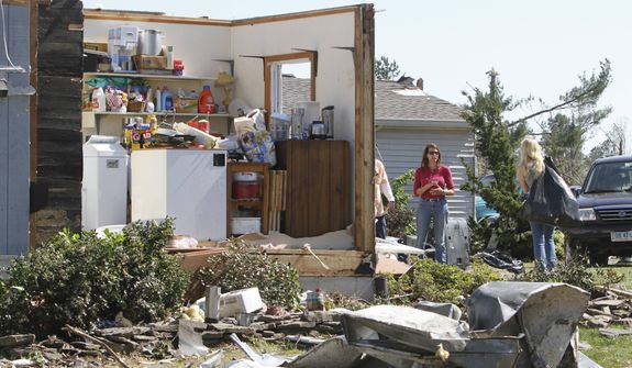 ** FILE ** Allison Cougill, center, helps sort through debris of her river cottage Sunday, April 17, 2011, after a tornado swept through the area Saturday in Deltaville, Va., Sunday, April 17, 2011. Tornadoes and flash flooding have left several people dead in Virginia, and crews are continuing to assess damage that severe weekend storms caused across several areas of the state. (AP Photo/Steve Helber)