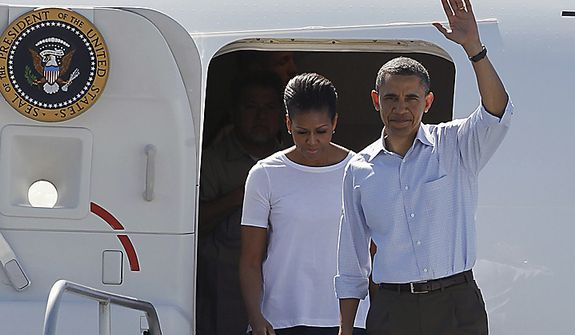 President Barack Obama, accompanied by first lady Michelle Obama, waves as they exit Air Force One in Tuscaloosa, Ala.,  Friday, April 29, 2011, prior to touring tornado damage. (AP Photo/Butch Dill)
