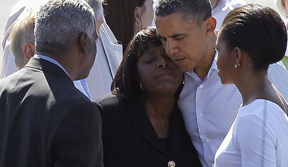 President Barack Obama hugs Rep. Terri Sewell, D-Ala., as first lady Michelle Obama and Birmingham, Ala. Mayor William Bell look on, Friday, April 29, 2011, in Tuscaloosa, Ala. (AP Photo/Butch Dill)