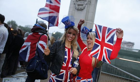 Royal enthusiasts celebrate at first light along the Royal Wedding route in London Friday, April, 29, 2011. (AP Photo/Elizabeth Dalziel)