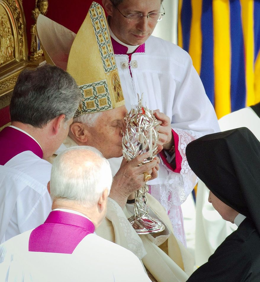 "Pope Benedict XVI kisses the glass reliquary containing the blood of the late Pope John Paul II. Speaking in Latin, Benedict pronounced John Paul ""Blessed"" shortly after the start of the Mass."