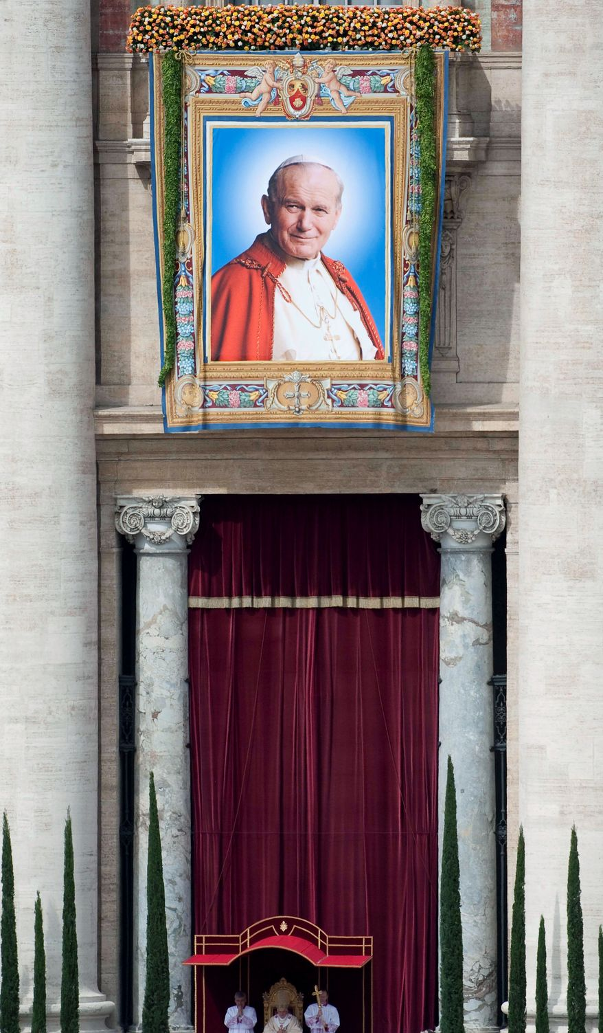 A tapestry bearing a 1995 picture of John Paul II is displayed during the Mass, which was watched by Catholics around the world.