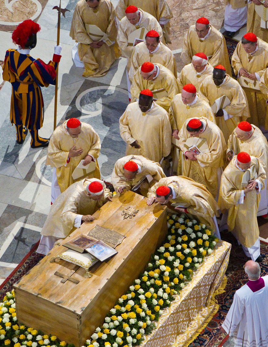 ASSOCIATED PRESS PHOTOGRAPHS Cardinals kiss the casket of Pope John Paul II at the end of a solemn celebration Sunday in St. Peter's Square. The beatification of the late pontiff by Pope Benedict XVI is the fastest in modern times.