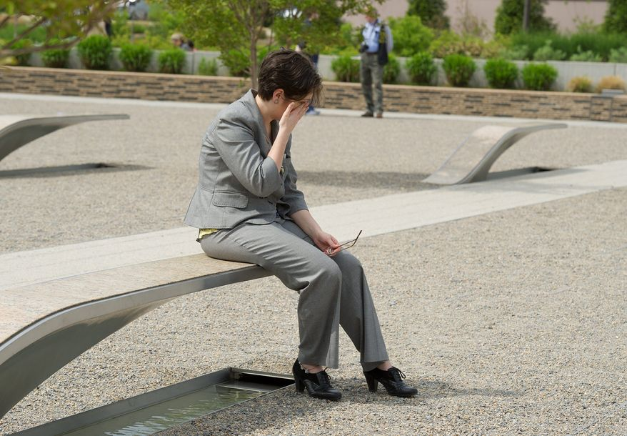 Pentagon employee Christy Heib wipes her eyes while sitting on a bench at the Pentagon Memorial in Arlington on Monday. Ms. Heib says the Sept. 11 attacks are why she began a government career. (Barbara L. Salisbury / The Washington Times)