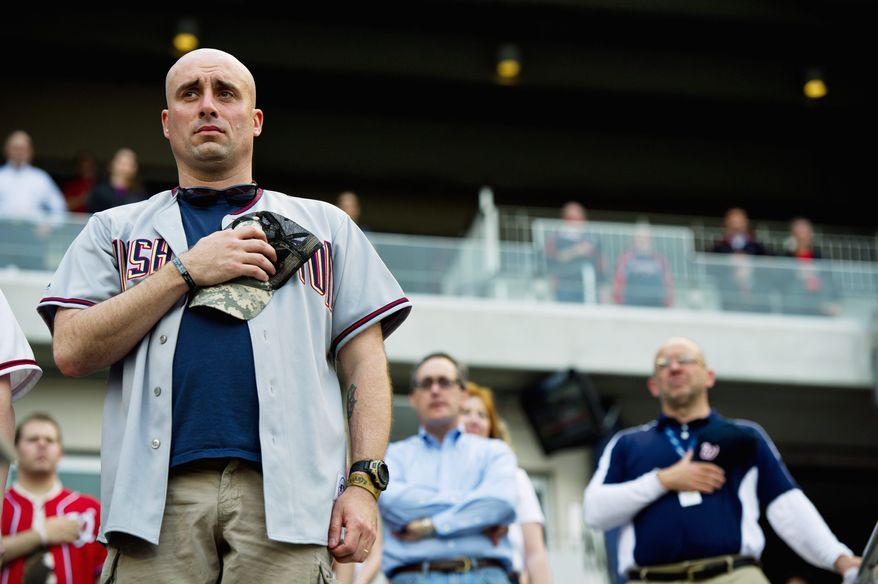 PHOTOGRAPHS BY DREW ANGERER/THE WASHINGTON TIMES Active Army Sgt. John Eastwood shows resepct during the national anthem on Military Appreciation Night before Washington played San Francisco at Nationals Park.