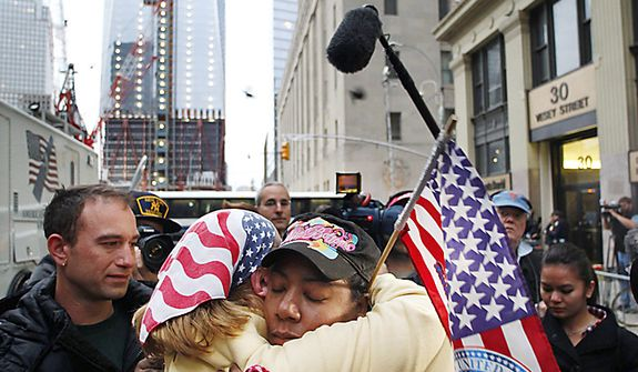 Dionne Layne, facing camera, hugs Mary Power as they react to the news of the death of Osama bin Laden, Monday, May 2, 2011 in New York. At left is the under construction 1 World Trade Center, also known as the Freedom Tower. (AP Photo/Mark Lennihan)