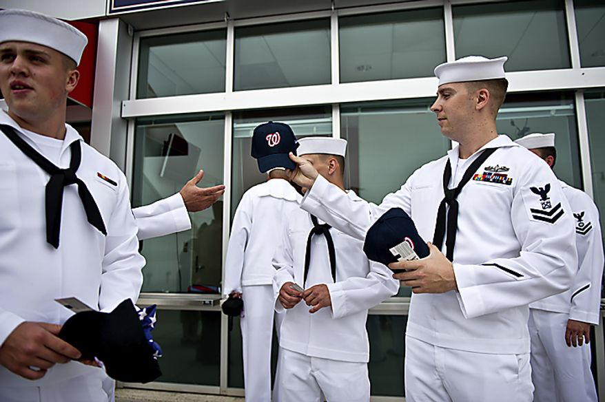 Naval petty officer Matt Cobb, right, passes out Nationals hats to fellow Navy service men that were given out to all active service members along with a free ticket during Military Appreciation Night at Nationals Park in Washington, D.C., Monday, May 2, 2011. The group was stopped outside the stadium by National community relations director Israel Negron, who informed them they were going to be given GM Mike Rizzo's field level seats for the evening. (Drew Angerer/The Washington Times)