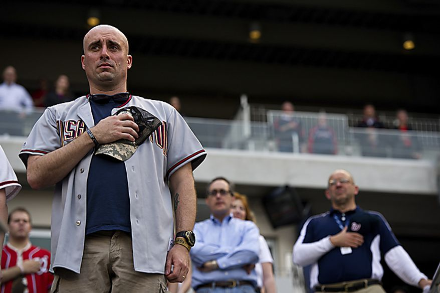Active Army Sgt. John Eastwood holds his cap over his heart during the National Anthem on Military Appreciation Night at Nationals Park, in Washington, D.C., Monday, May 2, 2011. He is stationed at Fort Meyer, Va. (Drew Angerer/The Washington Times)