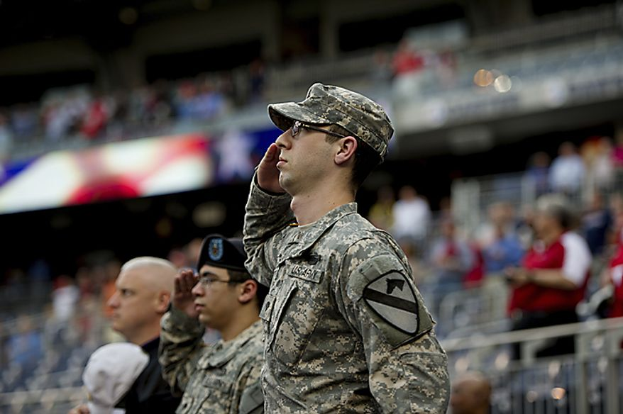 Active Army Spc. Sam Angert, right and active Army Spc. Daryl Pelland , center, salute toward the flag during the National Anthem on Military Appreciation Night at Nationals Park, in Washington, D.C., Monday, May 2, 2011. (Drew Angerer/The Washington Times)