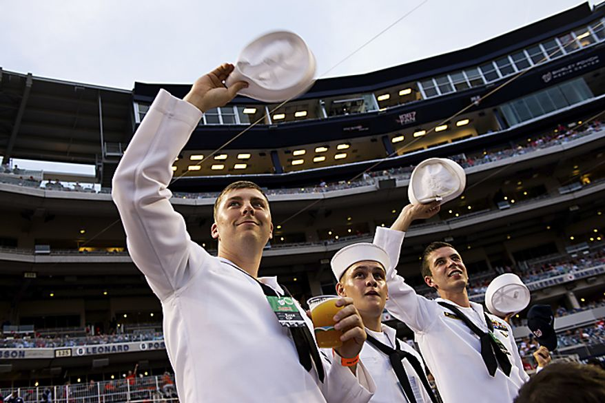 U.S. Navy Petty Officer Matt Cobb (center) and seamen Juan Sosa (center) and Oleksandr Chulovsky acknowledge the crowd's standing ovation at Nationals Park for military service men and women during Military Appreciation Night at the park in Washington, D.C., Monday, May 2, 2011. (Drew Angerer/The Washington Times)