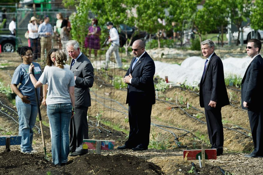 DREW ANGERER/THE WASHINGTON TIMES England's Prince Charles tours Common Good City Farm in Northwest on Tuesday during his first U.S. visit in four years. The 62-year-old prince is scheduled to meet Wednesday with President Obama to discuss the concept of sustainable agriculture.