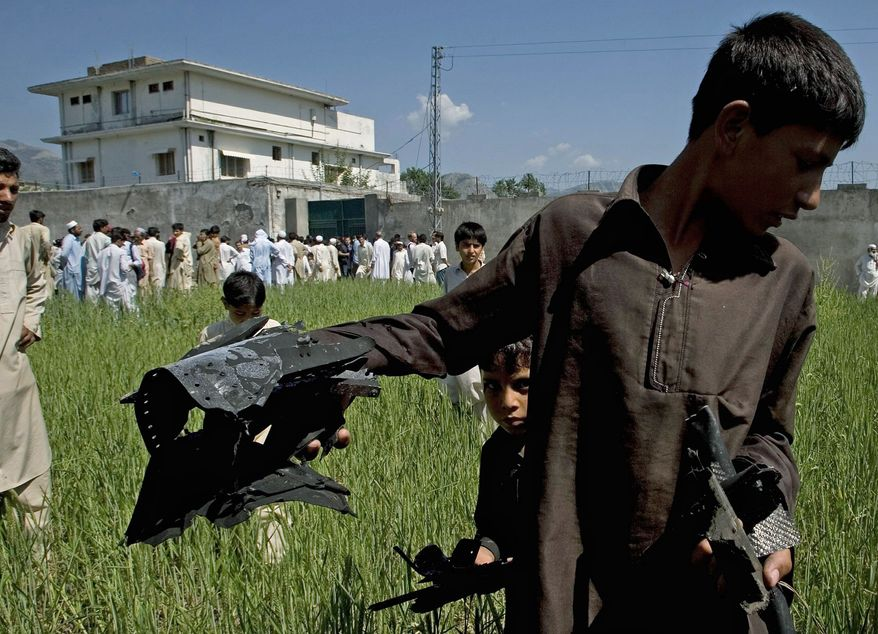 SCAVENGERS: Pakistani youngsters collect pieces thought to be from a U.S. helicopter in a wheat field outside Osama bin Laden's hide-out in Abbottabad, Pakistan, on Tuesday. The U.S. said the strike team disabled the helicopter after the raid. (Associated Press)