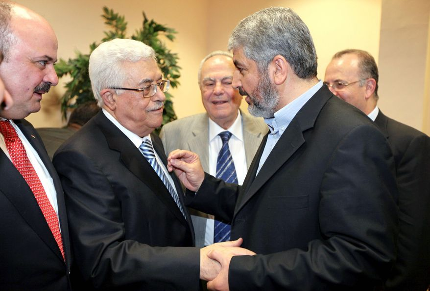 ASSOCIATED PRESS/HAMAS MEDIA OFFICE Palestinian President Mahmoud Abbas (center left) shakes hands with Hamas leader Khaled Mashaal in Cairo on Wednesday after agreement on a reconcilation pact. Left unresolved was who will lead the government to be formed. There was also no mention of relations with Israel.