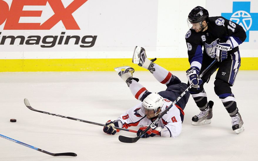 ASSOCIATED PRESS Capitals left wing Alex Ovechkin dives for the puck in front of the Lightning's Teddy Purcell during the second period of Game 4. The Lightning won 5-3 to sweep the Eastern Conference semifinal series.