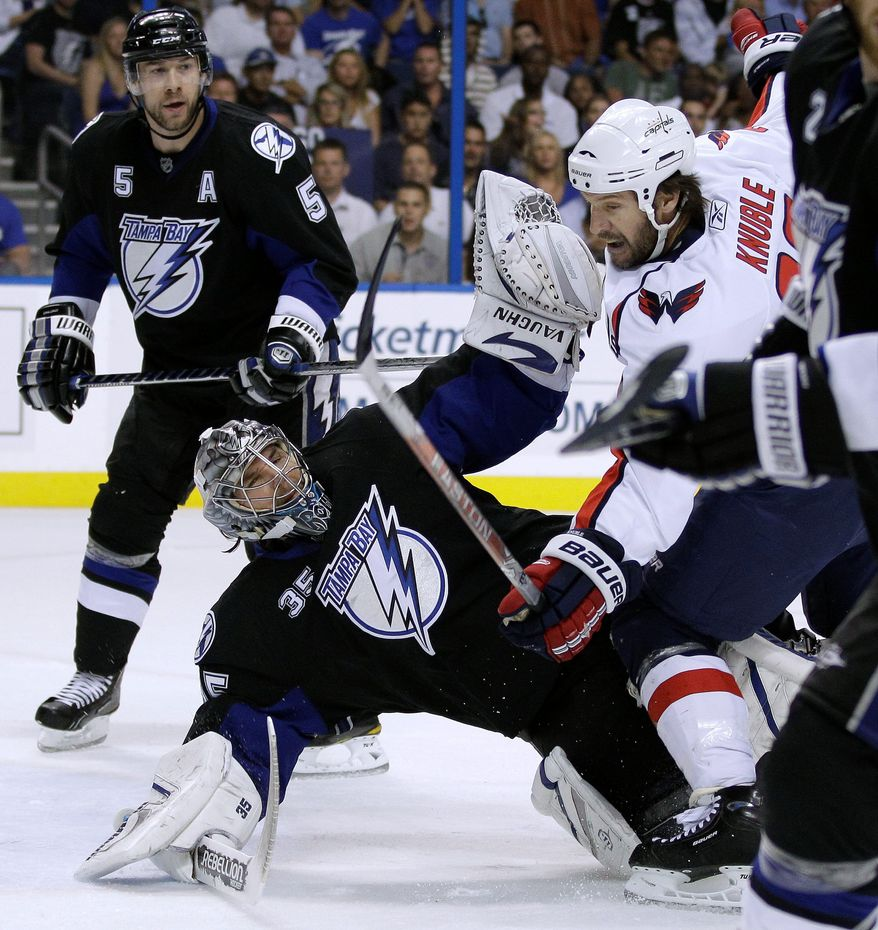 ASSOCIATED PRESS Capitals right wing Mike Knuble (22) collides with Lightning goalie Dwayne Roloson during the first period in Game 4 in Tampa, Fla. Knuble was called for a penalty on the play.