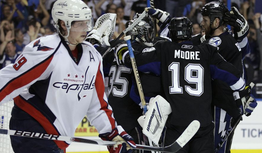 Tampa Bay Lightning players, including Dominic Moore (19) surround goalie Dwayne Roloson (35) as Washington Capitals center Nicklas Backstrom, left, of Sweden, skates toward the bench after the Lightning defeated the Capitals 5-3 in Game 4 of an NHL hockey Stanley Cup playoffs Eastern Conference semifinal series Wednesday, May 4, 2011, in Tampa, Fla., sweeping the series. (AP Photo/Chris O'Meara)