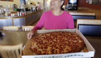 Waitress Jasmine Randhawa serves a pepperoni pizza at Mountain Mike's pizza parlor in Palo Alto, Calif., on Friday, April 1, 2011. The nation's service sector, which employs about 90 percent of the U.S. workforce, grew in April, though at the slowest pace since August. (AP Photo/Paul Sakuma)