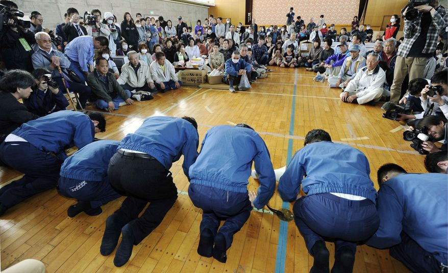 ASSOCIATED PRESS Tokyo Electric Power Co. President Masataka Shimizu, (third from right) bows in apology Wednesday to Namie villagers who have been living at an evacuation center in Fukushima prefecture since fleeing their homes, located in a 19-mile zone from the radiation-spewing Fukushima Dai-ichi nuclear plant.