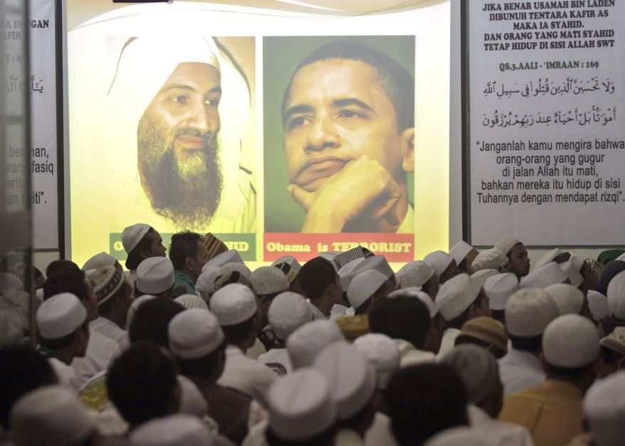PRAYERS: Members of the hard-line group Islam Defenders Front gather by portraits of Osama bin Laden and President Obama in Jakarta, Indonesia, during prayers Wednesday for the al Qaeda leader killed by U.S. forces in Pakistan. Mr. Obama is scheduled to meet Thursday with Sept. 11 families in New York. (Associated Press)