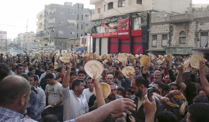 Syrian men carry bread loaves during a protest against President Bashar Assad's regime in the coastal town of Banias, Syria, on Tuesday, May 3, 2011, in this image taken by a citizen journalist with a cellphone camera. (AP Photo)