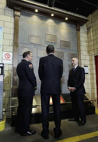 """U.S. President Barack Obama, center, views a memorial honoring deceased members of the New York City Fire Department during a visit to the headquarters of Engine Company 54, Ladder Company 4 and Battalion 9, in New York, U.S., on Thursday, May 5, 2011. The firehouse lost 15 members, the single largest loss of life of any firehouse among the 343 firefighters who died during the attack on the World Trade Center on Sept. 11, 2001. Obama will go to New York's """"Ground Zero"""" today, seeking to provide some closure to the worst terrorist attack on U.S. soil now that the world's most hunted terrorist, al-Qaeda leader Osama bin Laden, won't be """"walking on this earth again."""" Photographer: John Angelillo/Pool via Bloomberg"""