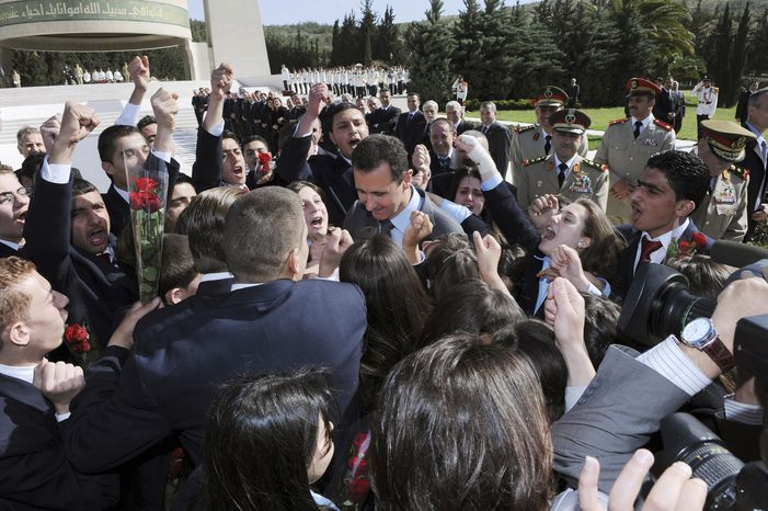 In this photo released by the Syrian official news agency SANA, Syrian students shout supportive slogans to Syrian President Bashar Assad (center) as he arrives Friday to lay a wreath at the tomb of the unknown soldier during Martyrs day in Kasiyoun mountain in Damascus, Syria. (Associated Press)