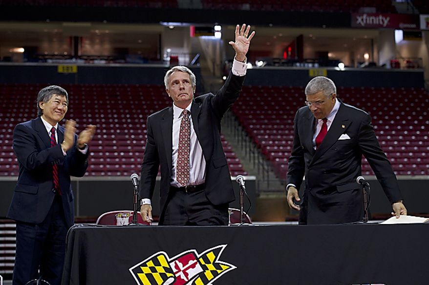Flanked by University of Maryland president Wallace Lowe, left, and diretor of athletics Kevin Anderson, coach Gary Williams gives one last wave to the crowd of Terps fans who came out to the Comcast Center in College Park, Md., on Friday, May 6, 2011 to officially say goodbye and thank him for his (...)