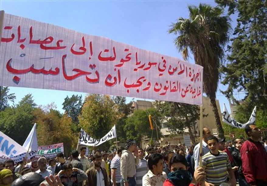 "In this citizen journalism image made on a mobile phone and acquired by the AP, taken on Friday, May 6, 2011, Syrian anti-government protesters carry a banner that reads in Arabic:""the security services has become out of laws and must be tried,"" during a rally in the central city of Homs, Syria. Syrian tanks rolled into Banias, a Mediterranean coastal town on Saturday May 7, 2011 in an escalating crackdown by President Bashar Assad, just a day after clashes with anti-government protesters that left tens of people dead nationwide, activists said. (AP Photo)"