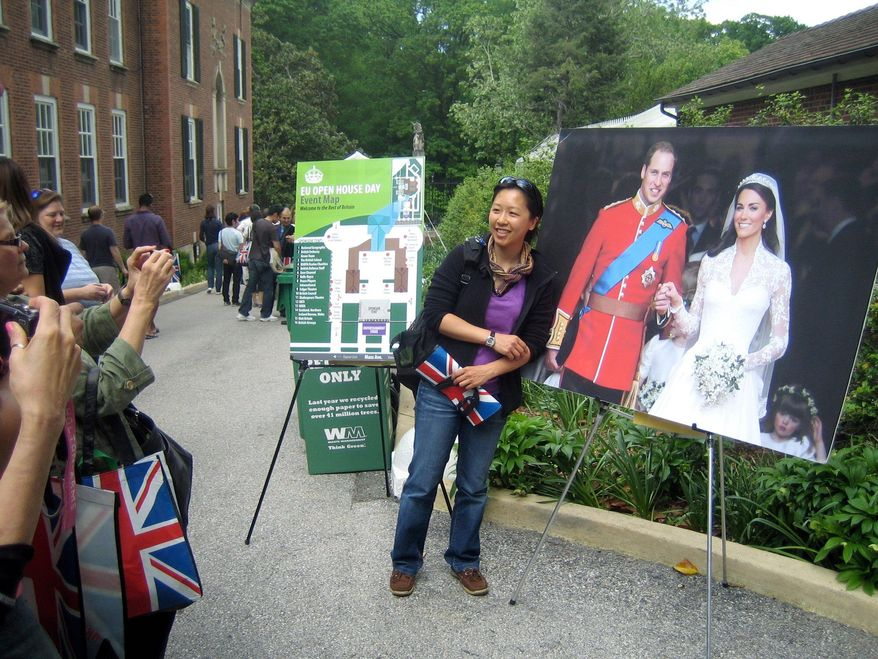MEREDITH SOMERS / THE WASHINGTON TIMES Rockville resident Kathy Huang poses Saturday with a photograph from the wedding of Prince William and Kate Middleton during the fifth annual European Union Open House. The events kicked off Europe Week, which runs through Friday.