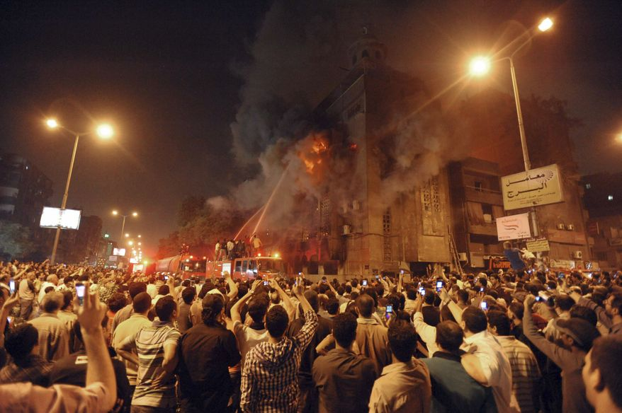 Firemen battle a fire at a church surrounded by angry Muslims in the Imbaba neighborhood in Cairo late on Saturday, May 7, 2011. (AP Photo)