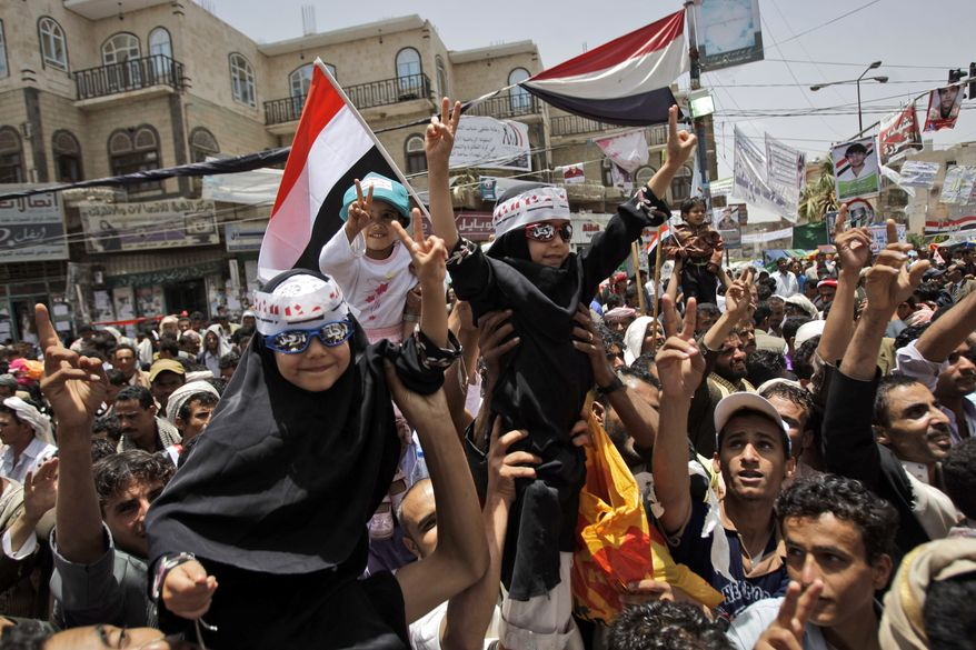 """Yemeni children, lifted by anti-government protesters, flash the victory sign during a demonstration demanding the resignation of Yemeni President Ali Abdullah Saleh in Sanaa, Yemen, on Sunday, May 8, 2011. The Arabic on their sunglasses says,"""" Leave."""" (AP Photo/Hani Mohammed)"""