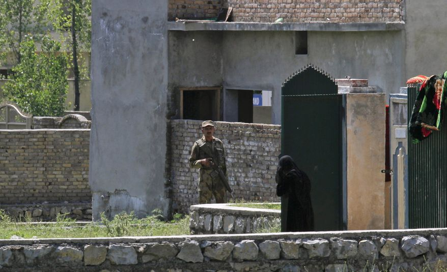 A Pakistani woman looks at an army soldier standing guard near the house of former al Qaeda leader Osama bin Laden in Abbottabad, Pakistan, on Sunday, May 8, 2011. Bin Laden was killed by a helicopter-borne U.S. military force on Monday in the fortresslike compound on the outskirts of the city. (AP Photo/Anjum Naveed)