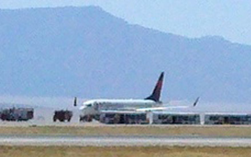 "A Delta Air Lines plane sits on the tarmac in a remote section of New Mexico's Albuquerque International Sunport on Sunday, May 8, 2011, after the flight, en route from Detroit to San Diego, was diverted over what authorities are calling a ""potential security threat."" (AP Photo/KRQE News 13, Katie Kim)"