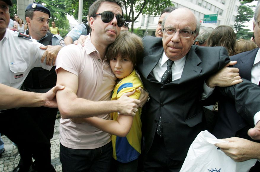 "ASSOCIATED PRESS ""They dragged him through the streets, for God's sake. That shows what they care about - and it wasn't him,"" said David Goldman of the day his son, Sean, was brought to the U.S. Consulate in Rio de Janeiro to be reunited with his father. He was accompanied by his Brazilian stepfather, Joao Paulo Lins e Silva (left), and attorney Sergio Tostes."