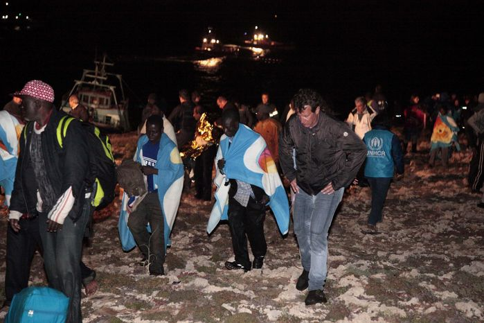 Migrants arrive Sunday on the tiny island of Lampedusa, Italy. Italian police and coast guard officials on Sunday rescued some 400 illegal migrants coming from Libya whose boat was tossed against rocks near port in southern Italy after the steering malfunctioned, officials said. (Associated Press)