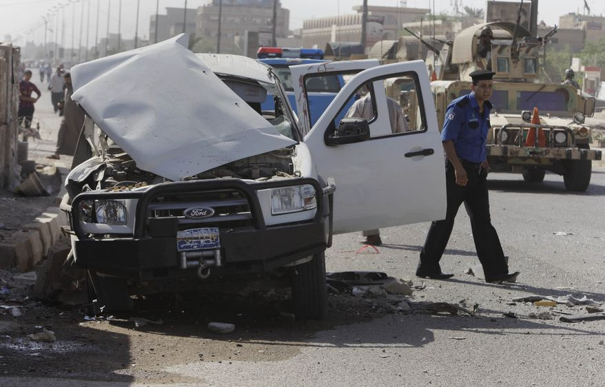 Iraqi security forces Monday inspect the scene of a roadside bomb attack in Baghdad targeting a police patrol, killing and wounding a few civilians, police said. (Associated Press)