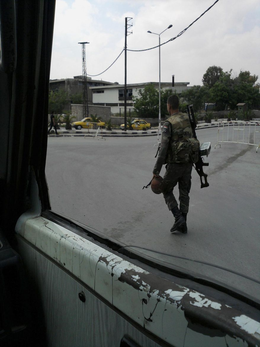 In this image taken on a mobile phone, a Syrian soldier patrols streets Sunday in Damascus, Syria. A 12-year-old boy was killed Sunday as gunfire and shelling erupted in the central Syrian city of Homs, a flashpoint in the widespread seven-week-old uprising against President Bashar Assad's autocratic regime, an activist said. (Associated Press)