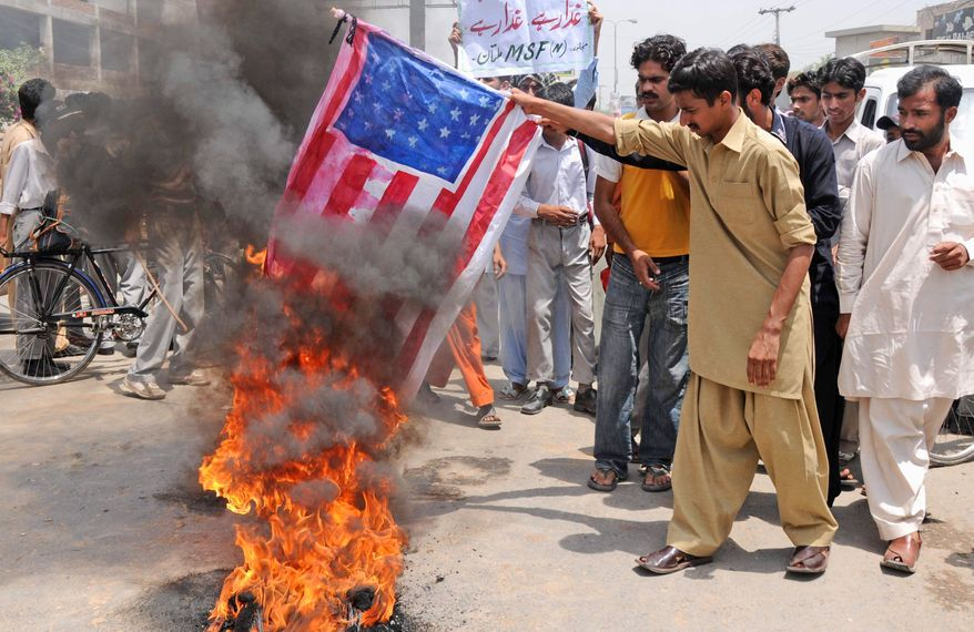 Supporters of Pakistan's Muslim League burn a representation of the U.S. flag during an anti-American demonstration Monday in Multan, Pakistan. Pakistan's prime minister is rejecting allegations that national authorities were either complicit in hiding al-Qaida chief Osama bin Laden or incompetent in tracking him down. (Associated Press)