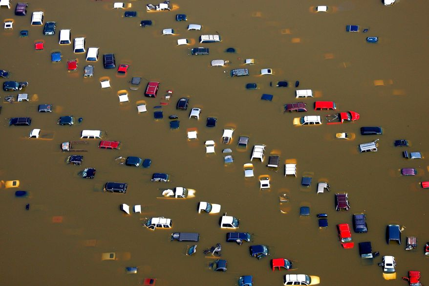 ASSOCIATED PRESS PHOTOGRAPHS Cars stand submerged in overflow water from the Wolf River on McMiller Road in Memphis, Tenn. After weeks of rising to historic levels, the Mississippi River reached a crest just shy of the forecasted 48 feet at the Memphis gauge.