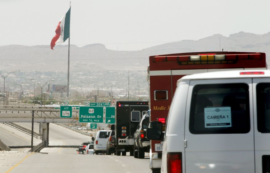 A Mexican flag flutters in the distance Tuesday as the motorcade of President Obama heads toward the Bridge of America Cargo Facility in El Paso, Texas, during his visit to the U.S.-Mexico border to speak about immigration reform. Mexico also had a giant flag at the border to remind Americans of the country's sovereignty. (Associated Press)