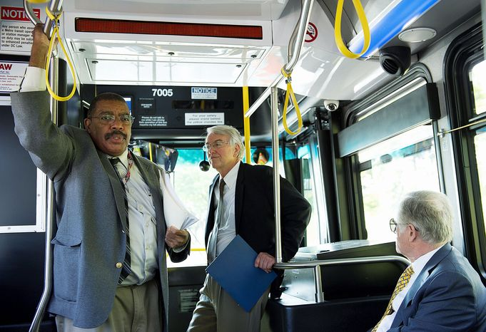 PHOTOGRAPHS BY BARBARA L. SALISBURY / THE WASHINGTON TIMES Metro officials (above, from left) Bob Golden, Jack Requa and Richard Sarles ride Tuesday on a new Xcelsior XDE40 bus while Robert Miles (below) drives. The new hybrid-electric models are about two feet shorter and 3,000 pounds lighter than existing Metro buses but can seat several more people.