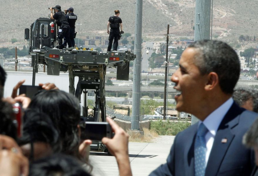 'ALLIGATORS IN THE MOAT': Security personnel scan the horizon as President Obama greets well-wishers after stepping off Air Force One at Biggs Army Airfield in El Paso, Texas, on Tuesday as he arrived at the U.S.-Mexico border to speak about immigration reform. (Associated Press)