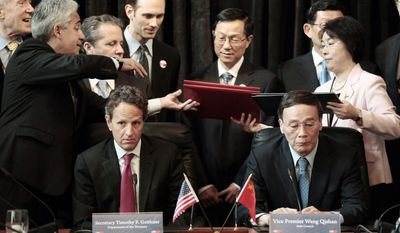 WORKING TOGETHER: Treasury Secretary Timothy F. Geithner and Chinese Vice Premier Wang Qishan wait as documents are exchanged during a signing ceremony on Tuesday in the Cash Room of the Treasury Department in Washington during the U.S.-China Strategic and Economic Dialogue meetings. (Associated Press)