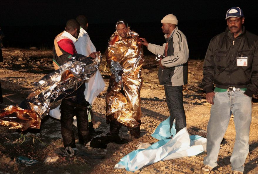 Migrants receive assistance as they arrive on the tiny Italian island of Lampedusa early on Sunday, May 8, 2011. Italian police and coast guard officials rescued some 400 migrants from Libya whose boat was tossed against rocks near the port in southern Italy after the steering malfunctioned, officials said. Tens of thousands have fled unrest in North Africa since January, most arriving at Lampedusa, the nearest Italian port to Africa. (AP Photo/Francesco Malavolta)