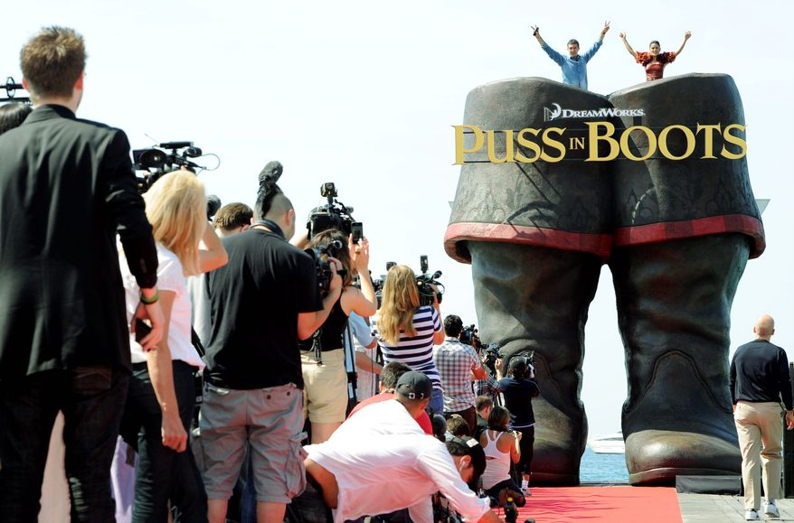 "ASSOCIATED PRESS PHOTOGRAPHS Mr. Banderas and  Miss Hayek pose atop a giant pair of boots while promoting their new film, ""Puss in Boots,"" at the Cannes Film Festival  on Wednesday. DreamWorks showed  off 15 minutes of the animated 3-D movie, a spin-off of the popular ""Shrek"" franchise."