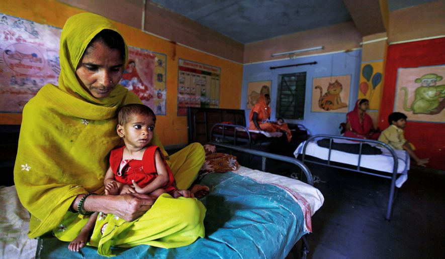 A woman named Shakila holds her too-thin daughter Sania at a government hospital ward for malnourished children in central India's Madhya Pradesh state. Nine out of 10 of the children are girls. (Associated Press)