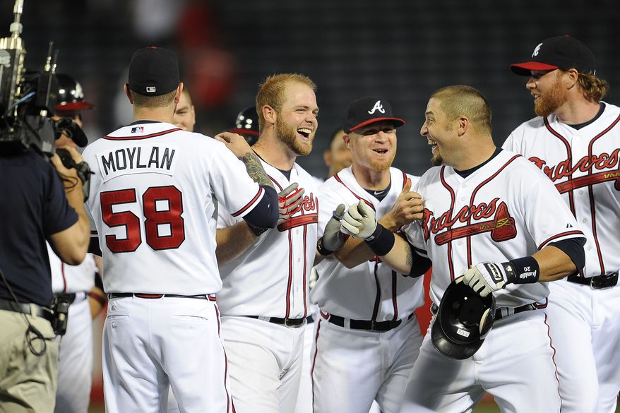 Atlanta Braves catcher Brian McCann, pictured right of relief pitcher Peter Moylan (58), is mobbed by his teammates after driving in the winning run during the 10th inning of a baseball game against the Washington Nationals on Thursday, May 12, 2011, in Atlanta. The Braves won 6-5 in 10 innings. (AP Photo/Paul Abell)
