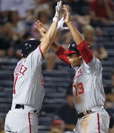 Washington Nationals' Alex Cora (13) and Ivan Rodriguez (7) celebrate after scoring on an Ian Desmond double in the 11th inning of a baseball game against the Atlanta Braves on Wednesday, May 11, 2011, in Atlanta. Washington won 7-3. (AP Photo/John Bazemore)